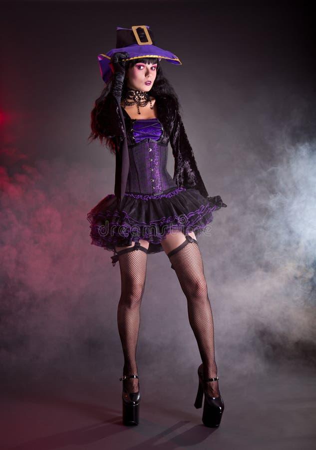 Όμορφη μάγισσα στο πορφυρό και μαύρο γοτθικό κοστούμι αποκριών στοκ φωτογραφίες με δικαίωμα ελεύθερης χρήσης