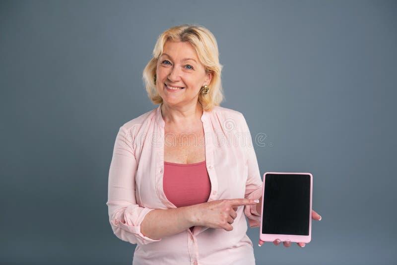 Όμορφη μέσης ηλικίας γυναίκα που προάγει μια ταμπλέτα στοκ εικόνες
