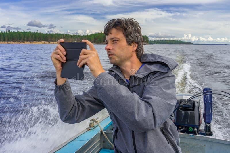 Όμορφη μέσης ηλικίας συνεδρίαση ατόμων στην πρύμνη βαρκών, που επιπλέει κατά μήκος της βόρειας λίμνης και που χρησιμοποιεί το sma στοκ φωτογραφίες με δικαίωμα ελεύθερης χρήσης