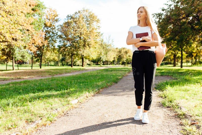 Όμορφη μαθήτρια που περπατά στο πάρκο που κρατά ένα βιβλίο σε ένα goo στοκ εικόνα