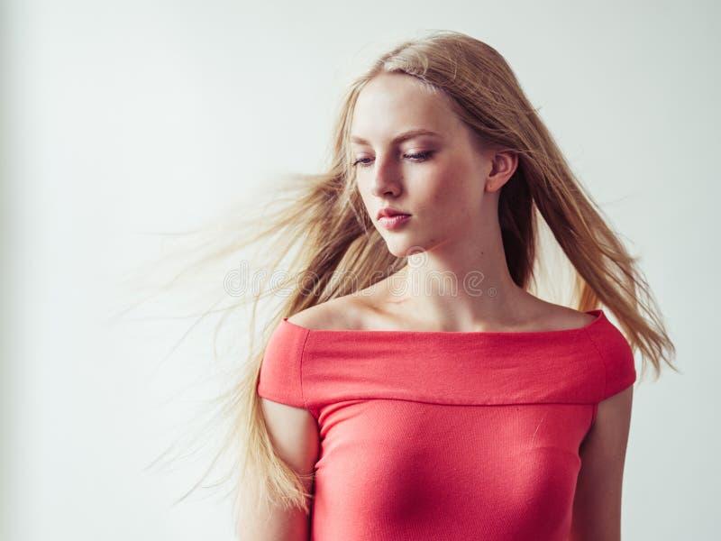 Όμορφη μακριά ξανθή γυναίκα τρίχας στο κόκκινο φόρεμα φυσικό πέρα από το λευκό στοκ εικόνες