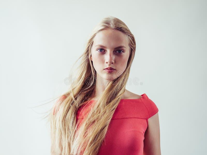 Όμορφη μακριά ξανθή γυναίκα τρίχας στο κόκκινο φόρεμα φυσικό πέρα από το λευκό στοκ φωτογραφίες