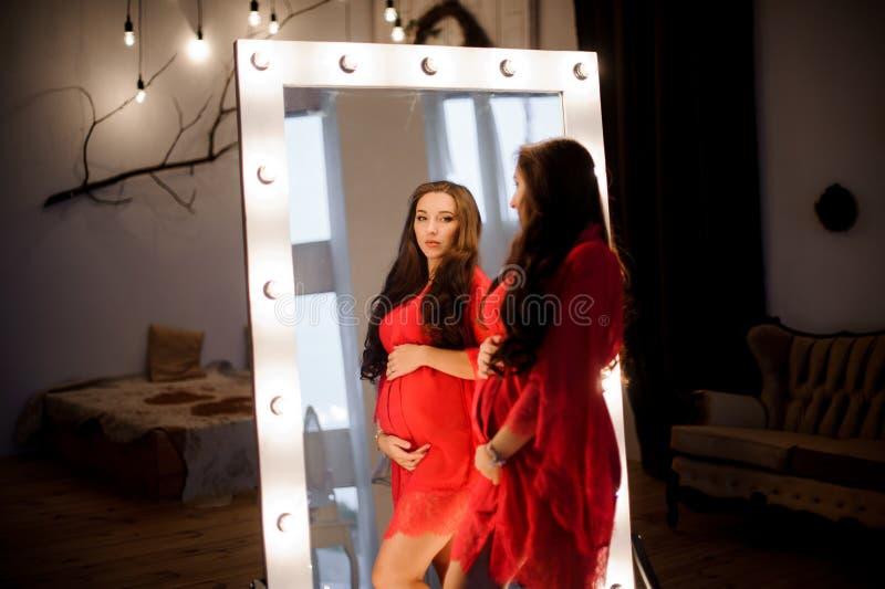 Όμορφη μακρυμάλλης έγκυος γυναίκα στη ρόμπα που κοιτάζει στον καθρέφτη στοκ φωτογραφία