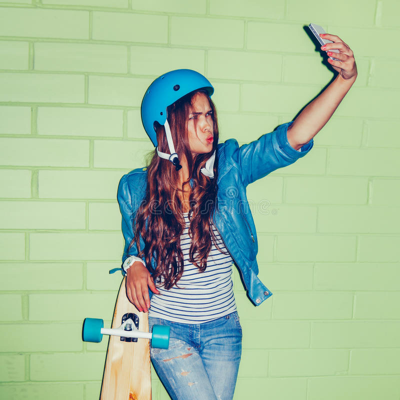 Όμορφη μακρυμάλλης γυναίκα με ένα smartpnone κοντά σε ένα πράσινο τούβλο στοκ φωτογραφία με δικαίωμα ελεύθερης χρήσης