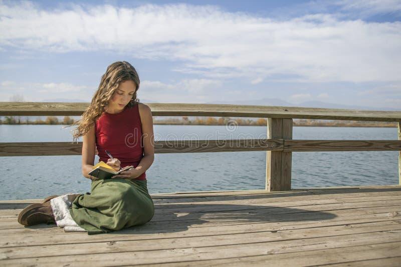 Όμορφη μακρυμάλλης γυναίκα που γράφει στο περιοδικό κοντά στην αγροτική λίμνη στοκ εικόνα