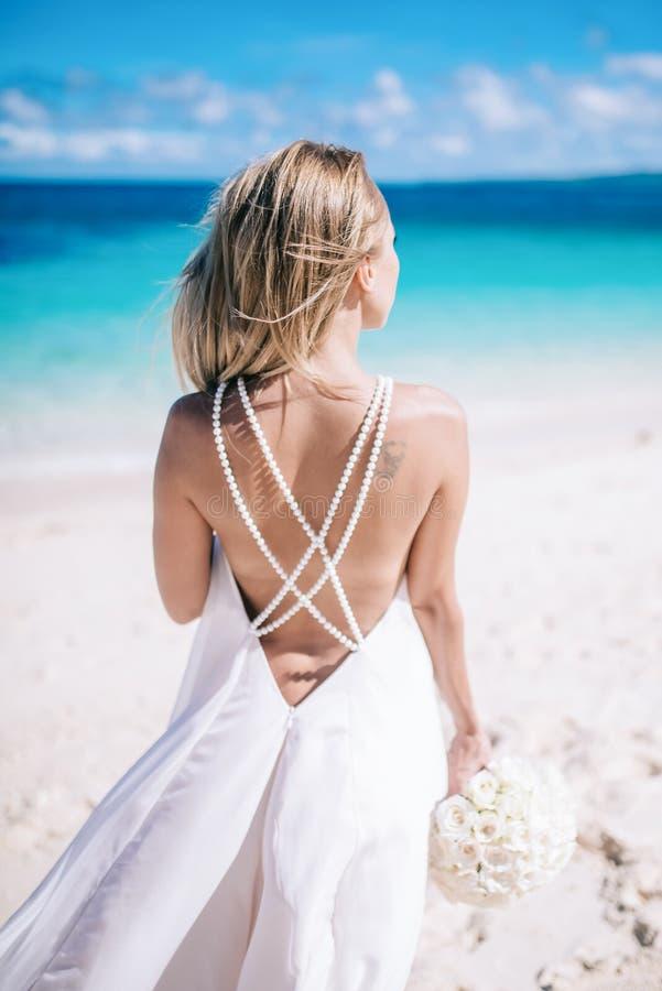 Όμορφη μακρυμάλλης νύφη στο πολύ άσπρο φόρεμα που στέκεται στην παραλία με άσπρο ανθοδεσμών στη θάλασσα στοκ εικόνες με δικαίωμα ελεύθερης χρήσης