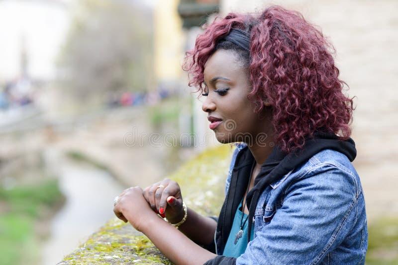 Όμορφη μαύρη γυναίκα στο αστικό υπόβαθρο με την κόκκινη τρίχα στοκ εικόνες