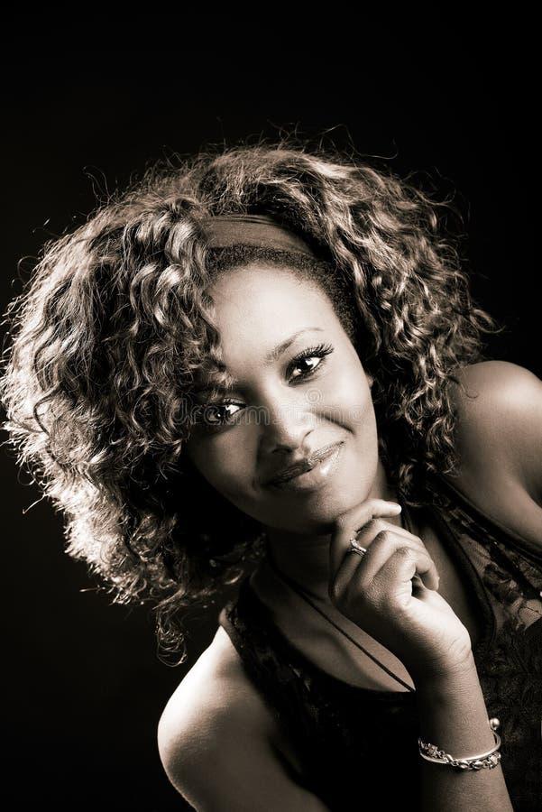 Όμορφη μαύρη γυναίκα στο μαύρο υπόβαθρο. Πυροβολισμός στούντιο στοκ εικόνα