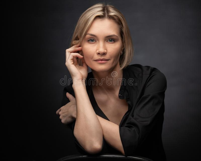 Όμορφη μεσήλικη γυναίκα με γκρι φόντο σε μαύρη μπλούζα στοκ φωτογραφίες με δικαίωμα ελεύθερης χρήσης