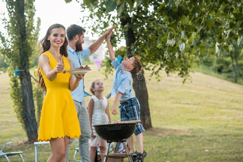 Όμορφη μητέρα που παρουσιάζει αντίχειρες ενώ ξοδεύοντας ποιοτικός χρόνος με την οικογένεια στοκ φωτογραφία με δικαίωμα ελεύθερης χρήσης