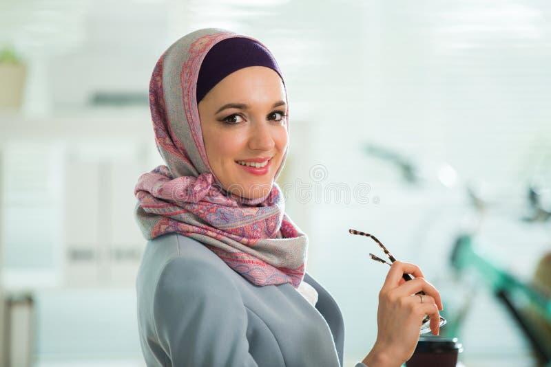 Όμορφη μοντέρνη γυναίκα στο hijab και eyeglasses, που κάθονται στο γραφείο με το lap-top στην αρχή στοκ φωτογραφίες