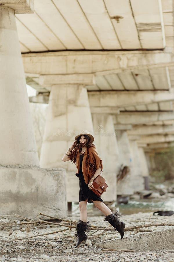 Όμορφη μοντέρνη γυναίκα hipster που πηδά, έχοντας τη διασκέδαση στο καπέλο, leat στοκ φωτογραφία