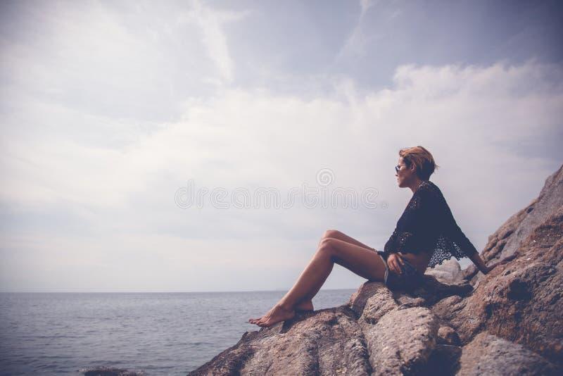 Όμορφη μοντέρνη νέα γυναίκα με τα μακριά πόδια που κάθεται στο μεγάλο ST στοκ φωτογραφίες με δικαίωμα ελεύθερης χρήσης