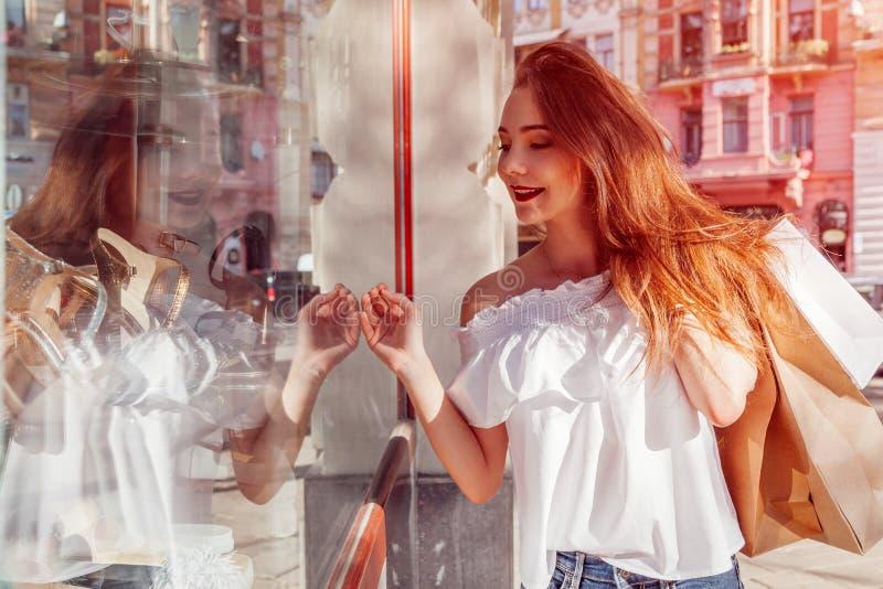 Όμορφη μοντέρνη νέα γυναίκα που περπατά με τις τσάντες αγορών στην οδό πόλεων και εξέταση την προθήκη ενός καταστήματος στοκ εικόνες