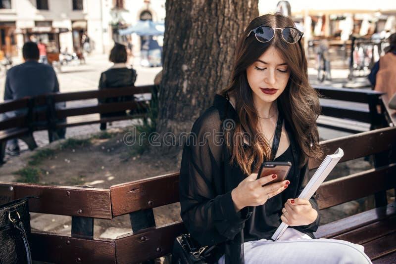 Όμορφη μοντέρνη συνεδρίαση γυναικών στον πάγκο στην οδό πόλεων, εκμετάλλευση στοκ φωτογραφία με δικαίωμα ελεύθερης χρήσης