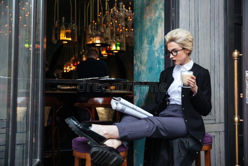 Όμορφη μοντέρνη συνεδρίαση κοριτσιών στον καφέ και το περιοδικό ανάγνωσης στοκ εικόνα με δικαίωμα ελεύθερης χρήσης