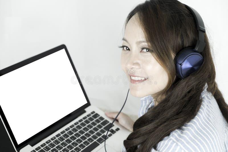 Όμορφη μουσική ακούσματος γυναικών στα ακουστικά στο κρεβάτι της Γυναίκα που βρίσκεται σε ένα άνετο κρεβάτι η έννοια χαλαρώνει Η  στοκ εικόνες με δικαίωμα ελεύθερης χρήσης