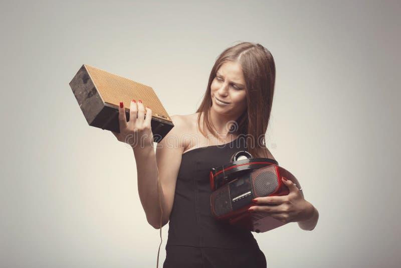 Όμορφη μουσική ακούσματος κοριτσιών μόδας Άσχημος στο ραδιόφωνο, με τα ακουστικά, ομιλητής, πικάπ, που φορούν τα κόκκινα γάντια,  στοκ φωτογραφία