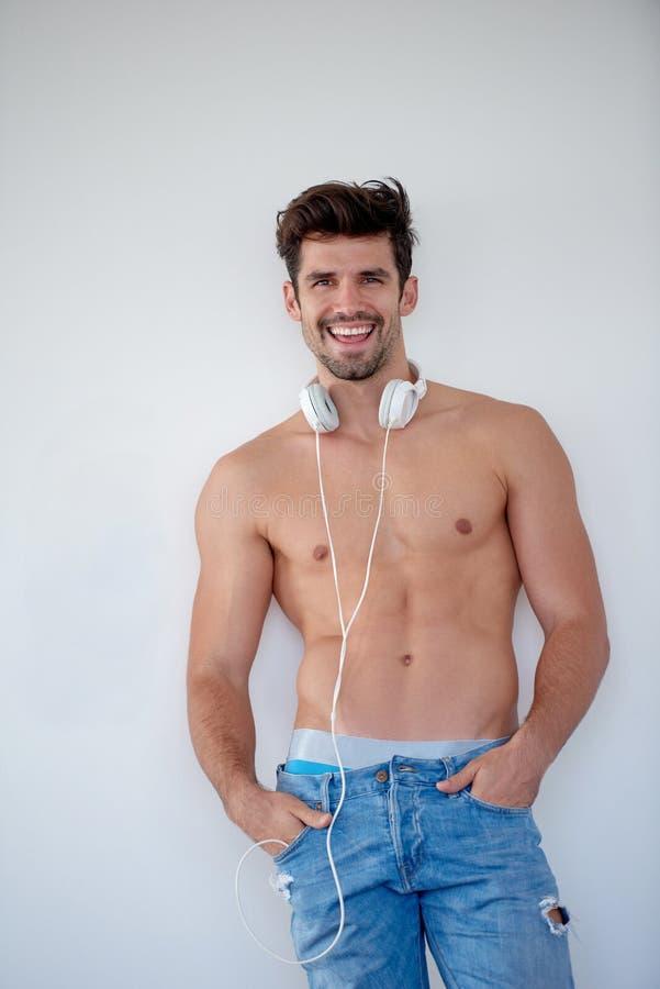 Όμορφη μουσική ακούσματος νεαρών άνδρων στα ακουστικά στοκ φωτογραφίες
