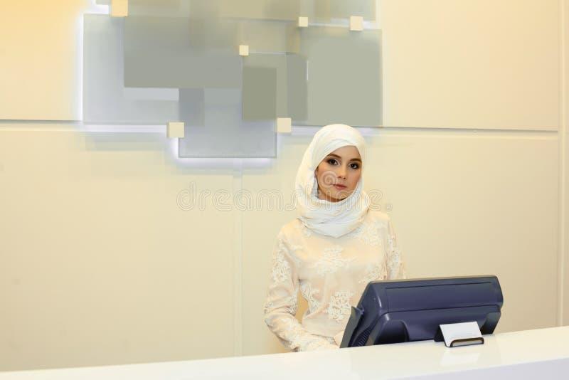 Όμορφη μουσουλμανική γυναίκα που στέκεται πίσω από την υποδοχή στο ξενοδοχείο στοκ φωτογραφία
