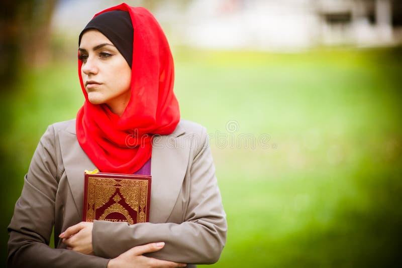 Όμορφη μουσουλμανική γυναίκα που φορά hijab και που κρατά ένα ιερό βιβλίο Koran στοκ εικόνα με δικαίωμα ελεύθερης χρήσης