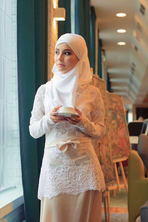 Όμορφη μουσουλμανική γυναίκα στο γαμήλιο φόρεμα με το φλυτζάνι του τσαγιού στα χέρια στοκ φωτογραφία