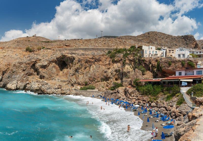 Όμορφη μπλε λιμνοθάλασσα με ομπρέλες στην αμμώδη παραλία, πόλη Chora Sfakion, Κρήτη στοκ εικόνες