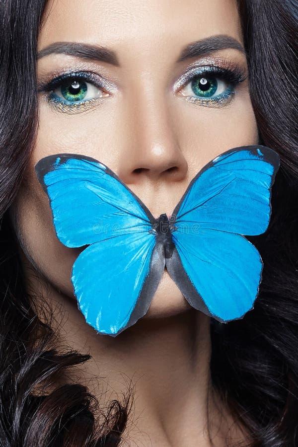 Όμορφη μυστήρια γυναίκα με το μπλε χρώμα πεταλούδων στις τεχνητές μπλε πεταλούδες της προσώπου, brunette και εγγράφου στα κορίτσι στοκ φωτογραφία με δικαίωμα ελεύθερης χρήσης