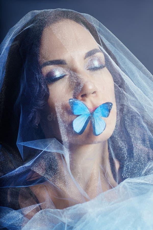 Όμορφη μυστήρια γυναίκα με το μπλε χρώμα πεταλούδων στις τεχνητές μπλε πεταλούδες της προσώπου, brunette και εγγράφου στα κορίτσι στοκ εικόνες