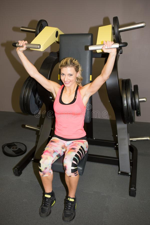Όμορφη μυϊκή κατάλληλη ξανθή γυναίκα που ασκεί τους μυς οικοδόμησης στη γυμναστική ικανότητας στοκ φωτογραφία με δικαίωμα ελεύθερης χρήσης