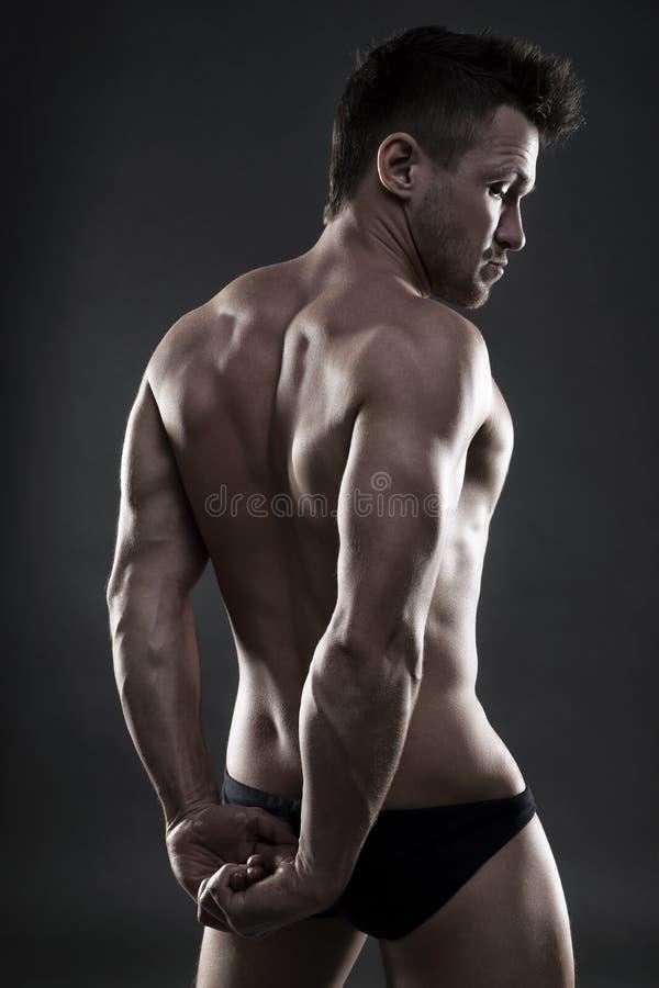 Όμορφη μυϊκή τοποθέτηση bodybuilder στο γκρίζο υπόβαθρο Συγκρατημένος πυροβολισμός στούντιο στοκ φωτογραφίες