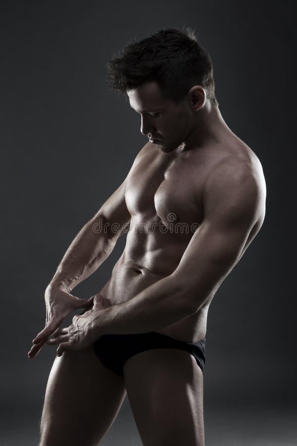 Όμορφη μυϊκή τοποθέτηση bodybuilder στο γκρίζο υπόβαθρο Συγκρατημένος πυροβολισμός στούντιο στοκ εικόνες