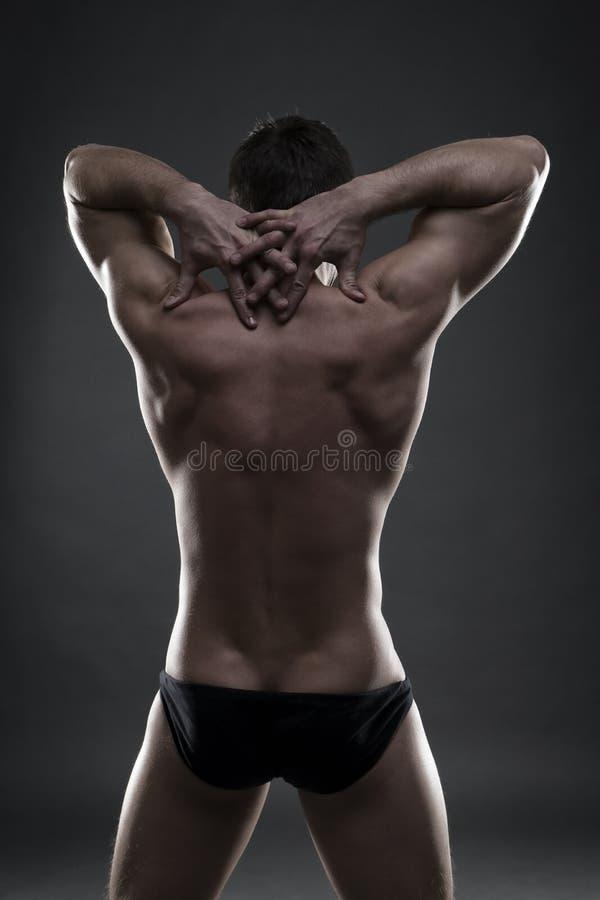 Όμορφη μυϊκή τοποθέτηση bodybuilder στο γκρίζο υπόβαθρο Συγκρατημένος πυροβολισμός στούντιο στοκ εικόνα