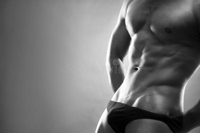 Όμορφη μυϊκή τοποθέτηση bodybuilder στο γκρίζο υπόβαθρο Συγκρατημένο γραπτό στούντιο που πυροβολείται με το διάστημα αντιγράφων στοκ εικόνα