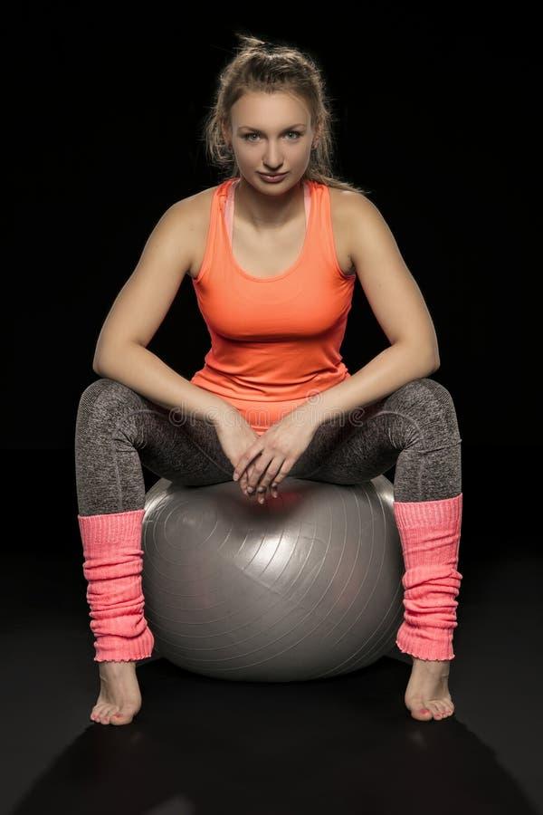 Όμορφη νέα αθλητική γυναίκα που ασκεί με μια σφαίρα γυμναστικής στοκ εικόνες με δικαίωμα ελεύθερης χρήσης