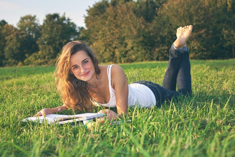 Όμορφη νέα ανάγνωση γυναικών σε ένα πράσινο λιβάδι στοκ εικόνες