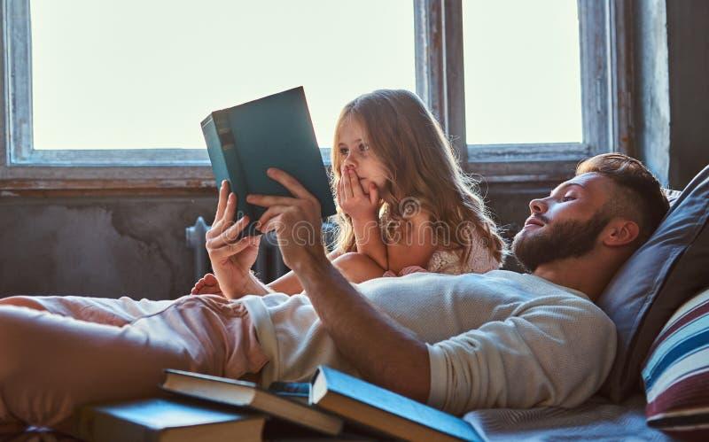 Όμορφη νέα ανάγνωση πατέρων storybook η μικρή κόρη του στο κρεβάτι στοκ εικόνα