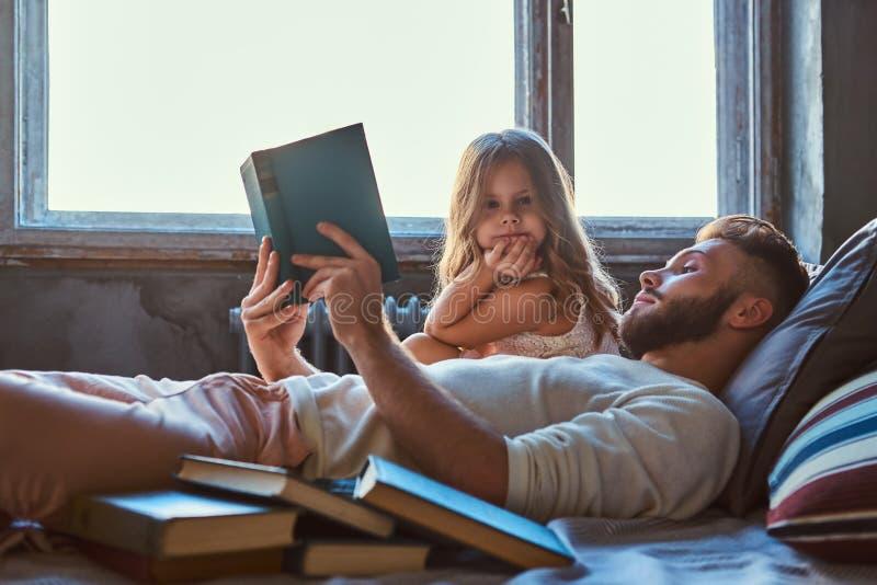 Όμορφη νέα ανάγνωση πατέρων storybook η μικρή κόρη του στο κρεβάτι στοκ εικόνες