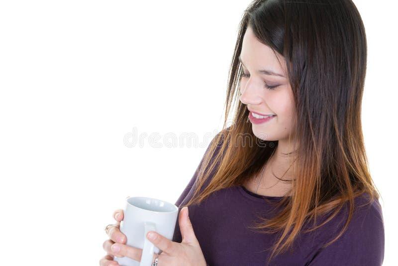 Όμορφη νέα απόλαυση γυναικών που φαίνεται φλιτζάνι του καφέ στοκ φωτογραφία