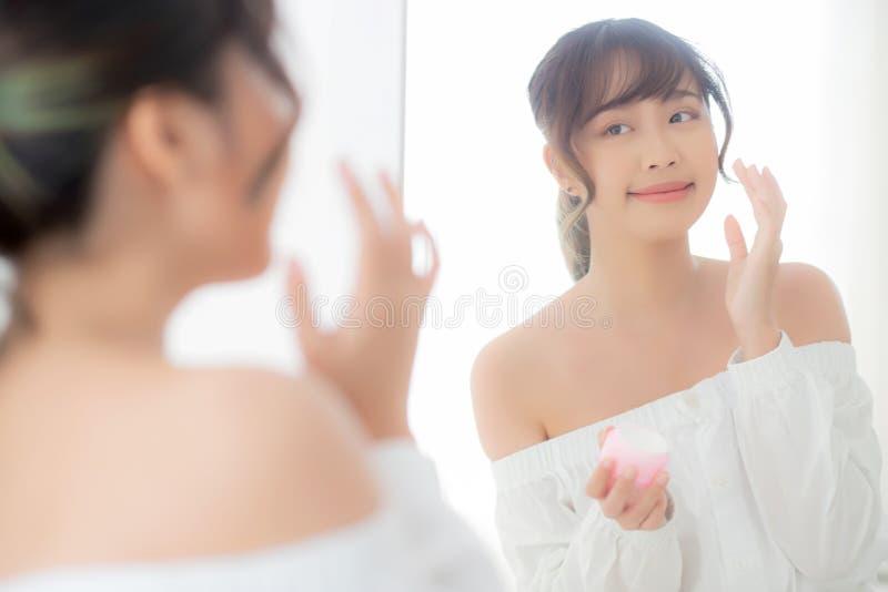 Όμορφη νέα ασιατική γυναίκα πορτρέτου που εφαρμόζει την κρέμα moisturizer ή το καλλυντικό φροντίδας δέρματος λοσιόν στο πρόσωπο π στοκ εικόνες