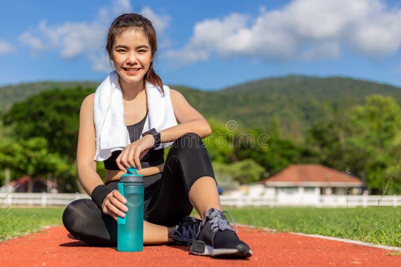 Όμορφη νέα ασιατική γυναίκα στη συνεδρίαση εξαρτήσεων ικανότητας στο τρέξιμο της διαδρομής και το χαμόγελο στη κάμερα σε έναν υπα στοκ εικόνες με δικαίωμα ελεύθερης χρήσης