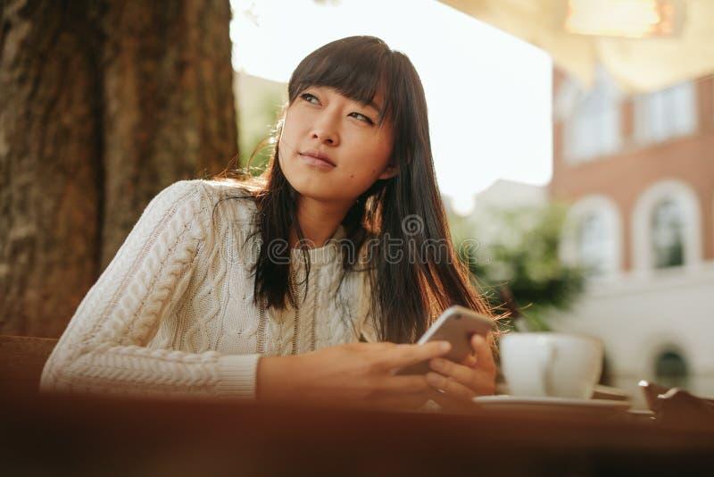 Όμορφη νέα ασιατική γυναίκα στον υπαίθριο καφέ στοκ φωτογραφίες