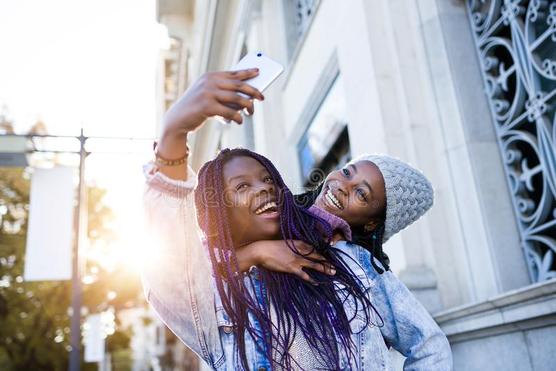 Όμορφη νέα γυναίκα δύο που χρησιμοποιεί το κινητό τηλέφωνο στην οδό στοκ εικόνες