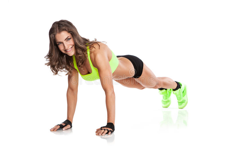 Όμορφη νέα γυναίκα ικανότητας που κάνει pushups στοκ φωτογραφία