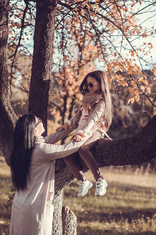 Όμορφη νέα γυναίκα και το παιδί της στον κήπο φθινοπώρου στοκ εικόνα με δικαίωμα ελεύθερης χρήσης