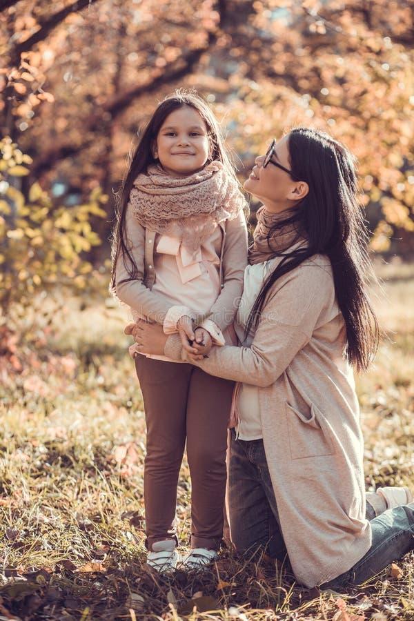 Όμορφη νέα γυναίκα και το παιδί της στον κήπο φθινοπώρου στοκ φωτογραφία