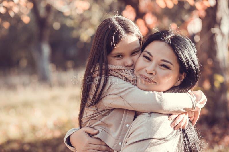 Όμορφη νέα γυναίκα και το παιδί της στον κήπο φθινοπώρου στοκ εικόνες