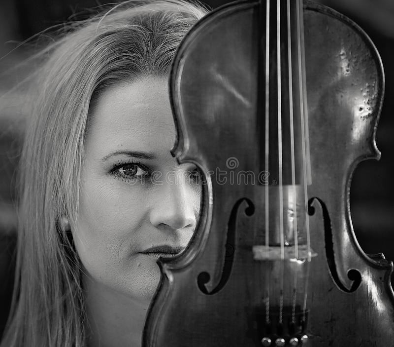 Όμορφη νέα γυναίκα κοντά μέχρι το παλαιό βιολί της στοκ φωτογραφίες με δικαίωμα ελεύθερης χρήσης