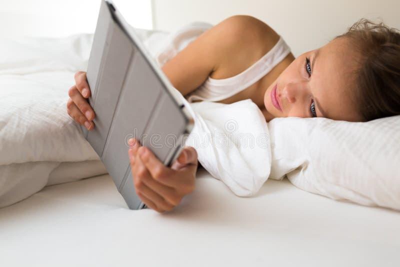 Όμορφη, νέα γυναίκα με έναν υπολογιστή ταμπλετών στο κρεβάτι της στοκ εικόνα