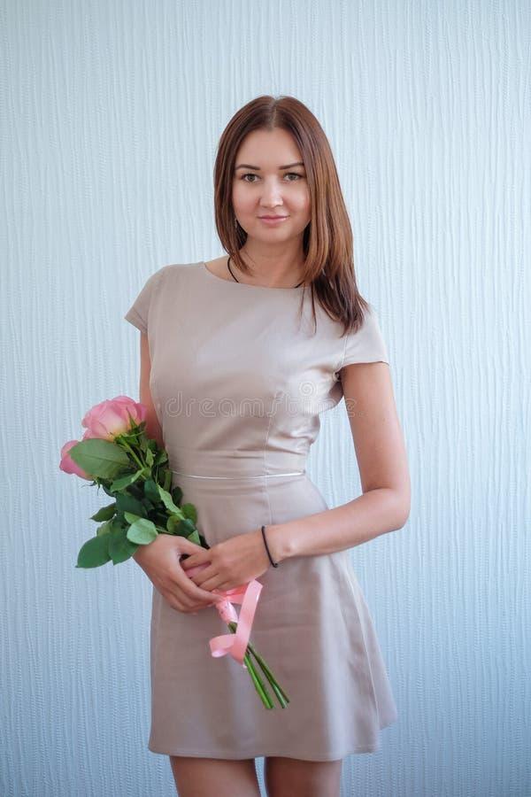Όμορφη νέα γυναίκα με μια ανθοδέσμη των τριαντάφυλλων στοκ φωτογραφία